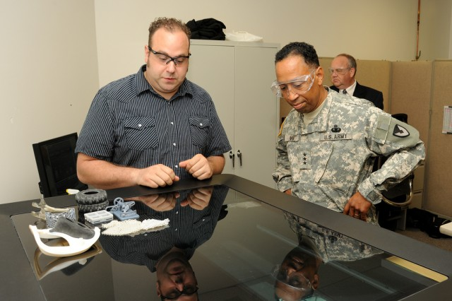 Brad Ruprecht, left, of ECBC's Advanced Design and Manufacturing Division, explains the 3-D printing process to Lt. Gen. Dennis Via, Army Materiel Command deputy commanding general.