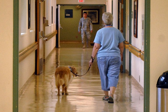 Human Animal Bond team Ruie Gibson and her golden retriever-border collie mix Millie walk down a hallway at Munson Army Health Center to begin an afternoon of visiting with patients and staff June 23, 2011, at Fort Leavenworth, Kan.
