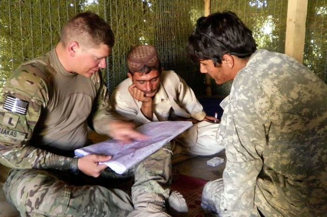 First Lt. Theodore Leakas, 2nd Battalion 8th Field Artillery Regiment, 1st Stryker Brigade Combat Team, 25th Infantry Division, discusses ways to reduce smuggling in Afghanistan's Daman district with an Afghan Border Patrol team leader.