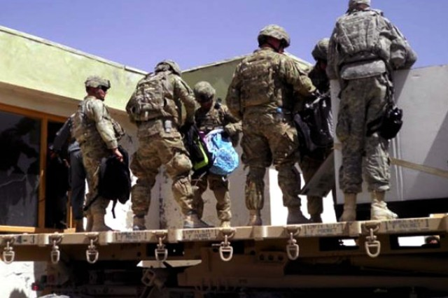 Soldiers from 2nd Battalion, 8th Field Artillery Regiment, 1st Stryker Brigade Combat Team, 25th Infantry Division, help deliver school supplies to a village in Aghanistan's Daman district.