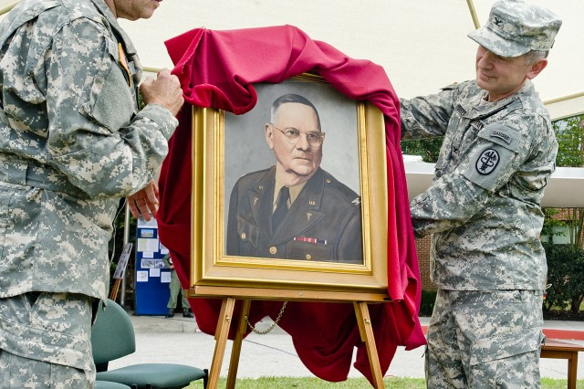 Col. Leon E. Moores, commander of the Fort Meade U.S. Army Medical Department Activity and Kimbrough Ambulatory Care Center, and Col. Dale K. Block, commander of the Pentagon's DiLorenzo TRICARE Health Clinic and former Kimbrough commander, unveil a portrait of Col. James Claude Kimbrough, the outpatient facility's namesake at a ceremony held on the KACC lawn.