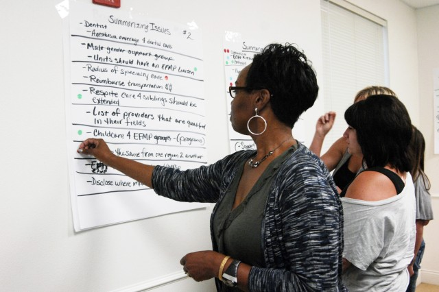 Gwen James, a participant in the AFAP EFMP Focus Forum, places a sticker next to one of her choices for the top issues of the forum. The top three issues from the forum will be included on the list of issues from the Fort Hood Army Family Action Plan Conference in the fall.