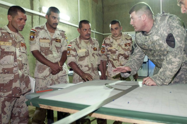 CONTINGENCY OPERATING SITE MAREZ, Iraq – Staff Sergeant Matthew Spurling, a field artilleryman assigned to Battery B, 5th Battalion, 82nd Field Artillery Regiment, 4th Advise and Assist Brigade, 1st Cavalry Division, shows 2nd Iraqi Army Division soldiers advanced fire direction procedures during a class at the Ghuzlani Eagle Training Site, Iraq, June 21, 2011. Spurling, a native of Killeen, Texas, and other Battery B Soldiers, teach Iraqi soldiers to operate and fire M198 155mm howitzers.