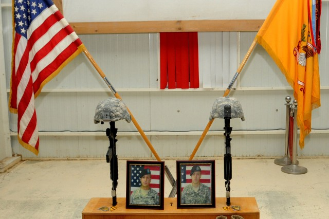 CONTINGENCY OPERATING SITE COBRA, Iraq – The portraits of Staff Sgt. Russell Proctor, 25, and Pfc. Dylan Johnson, 20, both cavalry scouts with Troop C, 4th Squadron, 9th Cavalry Regiment, 2nd Advise and Assist Brigade, 1st Cavalry Division, sit on display along with Soldiers' Battle Crosses as the centerpiece for a memorial ceremony at Contingency Operating Site Cobra, Iraq, June 28, 2011. Soldiers gathered to pay respect to the fallen Soldiers and honor their memories.
