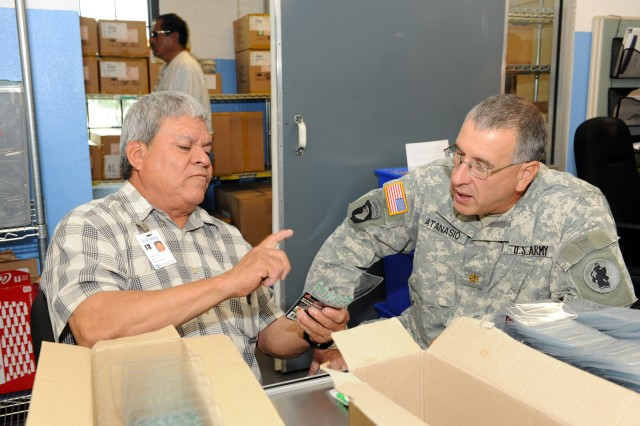 SAN ANTONIO – San Antonio Lighthouse for the Blind employee Gregorio Duran (left) describes some of the products he makes to Chaplain (Maj.) Charles Atanasio, from the U.S. Army South Chaplain's Office, at the SALB Jun. 23.