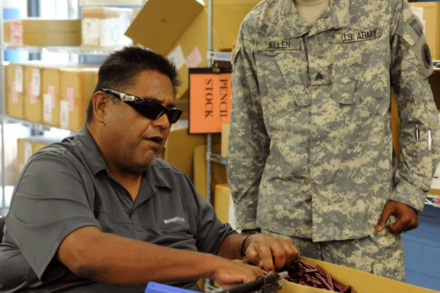 SAN ANTONIO – San Antonio Lighthouse for the Blind employee Henry Martinez (left) describes his job to Sgt. Harlowe Allen at the SALB Jun. 23.