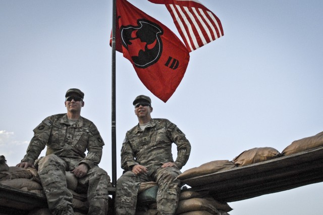 Staff Sgt. Rich Fiedler, left, a supply sergeant with Company A, 1st Battalion, 133rd Infantry Regiment, and his brother, Sgt. 1st Class Tim Fiedler, right, the acting first sergeant of Company A, sit together June 14, 2011, on Combat Outpost Najil in Laghman province, Afghanistan. The Fiedler brothers have served more than 50 years combined as Soldiers in Company A.