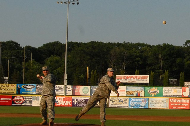 TROY, N.Y.--New York Army National Guard Soldiers 1st Sgt. Joseph Landy (left), and his son Pfc. Joseph Landy (right), throw the opening pitches in the Tri-City ValleyCats minor league baseball game here on July 5.