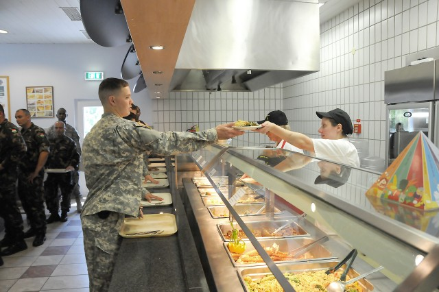 Pvt. David Hemme, 2nd Stryker Cavalry Regiment, samples the turkey yakisoba and glazed green beans during the Go for Green lunch at Rose Barracks' Stryker Inn, June 22.