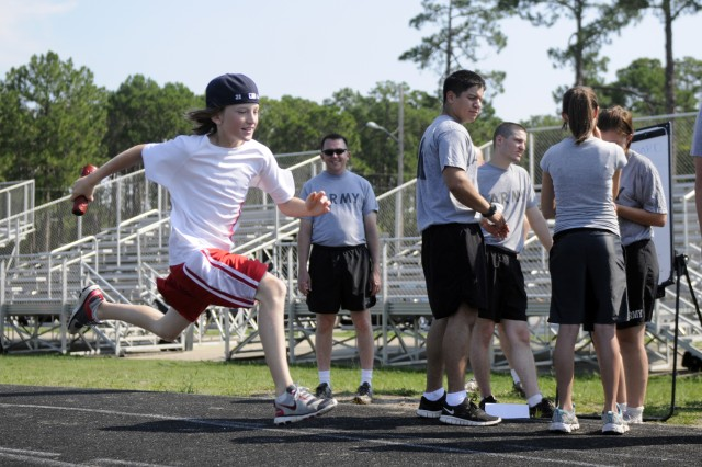 """Charging towards the finish line during a relay race, the child of a Soldier from 1/3 Brigade Special Troops Battalion, 1st Heavy Brigade Combat Team, gives everything he's got during the battalion's """"Family Fitness day,"""" July 1."""