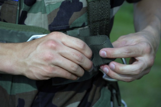 Cadet Senior Airman Jeremy Shaver folds the free running end on the harness' chest strap June 29 during an airborne class for 15 cadets from the Civil Air Patrol Harrisburg International Composite Squadron 306 on the 193rd Special Operations Wing Pennsylvania Air National Guard Base.