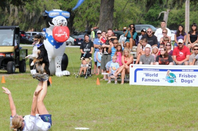 "Spencer, balances on his trainer's feet during the Frisbee Dog Show at Hunter's ""Worth Fighting For"" celebration July 2."