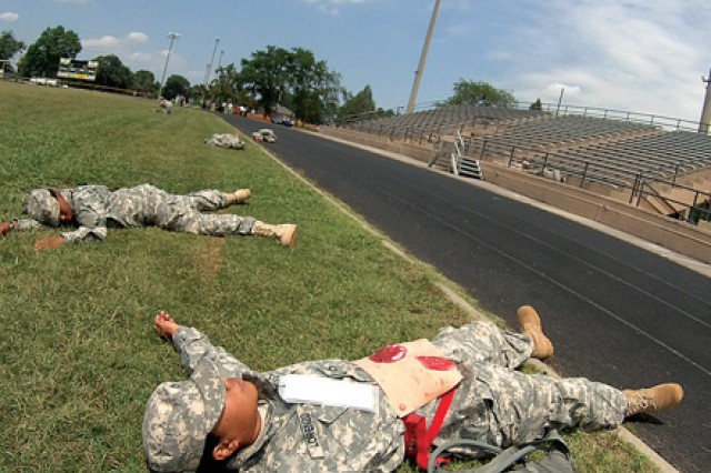 Military casualty role players lie about the Williams Stadium field after a mock terrist shooting.