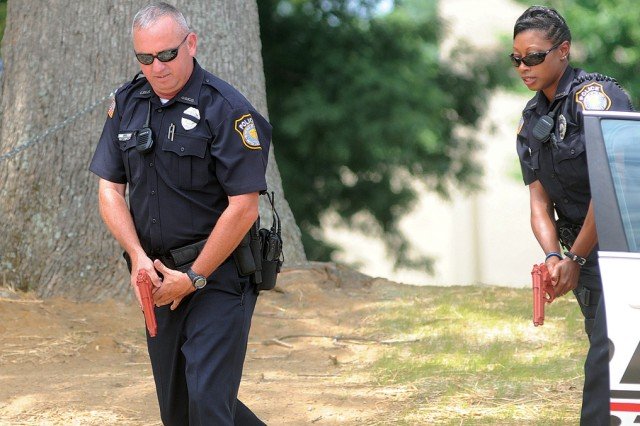 Fort Lee Police Department Officers Kevin Dee and Mysha Goins creep toward cover in helping to secure the perimeter.