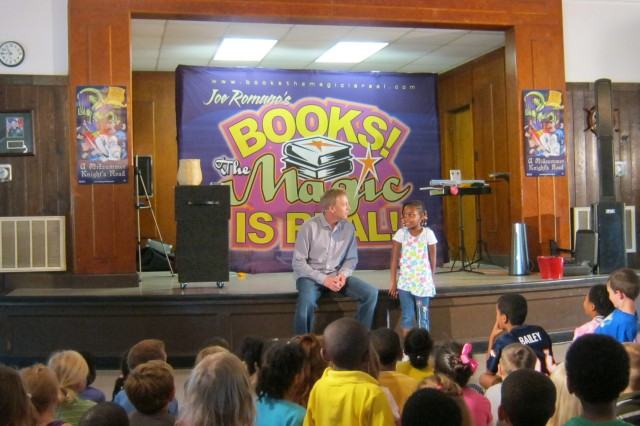 """Robertsha Mertzger, 5, participates in a magic trick with magician Joe Romano during his show """"Books -- The Magic Is Real 2"""" on June 28 at Burba Lake Cottage. The show kicked off Fort Meade's annual summer reading program sponsored by the Medal of Honor Memorial Library."""