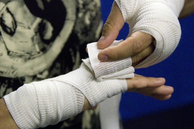 David Perez, leader and trainer of Team Warfighter, wraps his hands before a mixed martial arts training session. Perez and five other mixed martial arts fighters train at Gaffney Fitness Center twice a day, five days a week.
