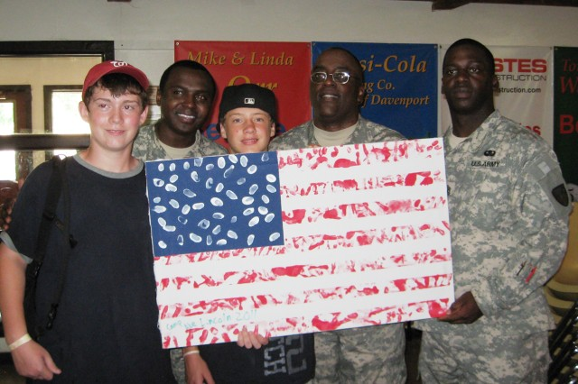 Col. Richard Dix (2nd from right), Army Sustainment Command chief of staff, accepts a handmade American flag from military children at Camp Abe Lincoln, Buffalo, Iowa. Dix, accompanied by Sgt. Maj. Ron Brooks (left) and 1st Sgt. Eric Evans (right), spoke with several dozen military children. (U.S. Army photo by Dan Carlson)