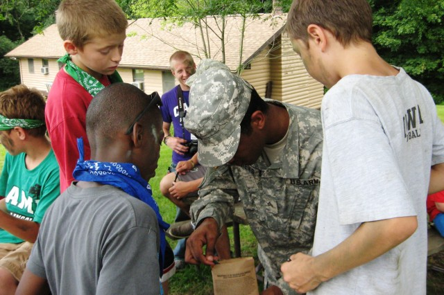 Curious campers examine an MRE - a packaged  military meal - in the hands of an Illinois Army National Guard Soldier. The hungry trio was among several dozen children at Camp Abe Lincoln, Buffalo, Iowa. (U.S. Army photo by Dan Carlson)