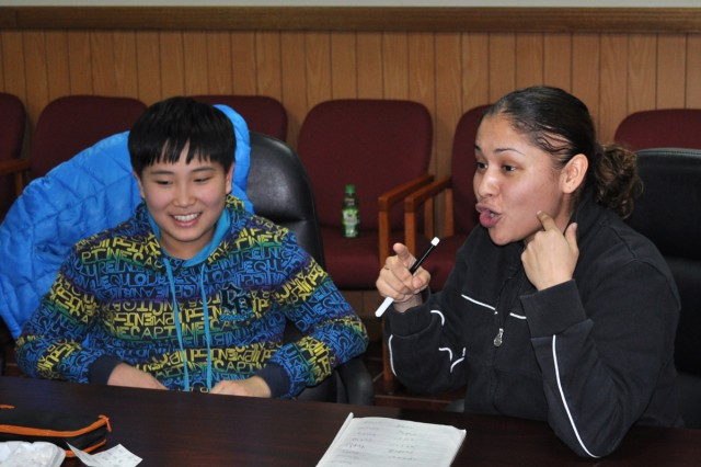 Staff Sgt. Clementina Cano-Perez (right), Headquarters Battery, 6-52nd Air Defense Artillery Battalion, teaches English to ROK Air Force children during the weekly Suwon Air Base English program July 6.
