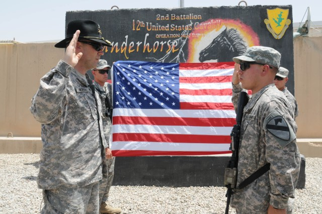 CONTINGENCY OPERATING SITE MAREZ, Iraq – Colonel Brian Winski, commander of 4th Advise and Assist Brigade, 1st Cavalry Division, re-enlists Sgt. Jessie Wilson, an infantryman assigned to Company B, 2nd Battalion, 12th Cavalry Regiment, attached to 1st Advise and Assist Task Force, 1st Infantry Division, during a ceremony at Contingency Operating Site Warrior, July 4, 2011. Wilson, a native of Bronx, N.Y., is currently on his second deployment to Iraq.