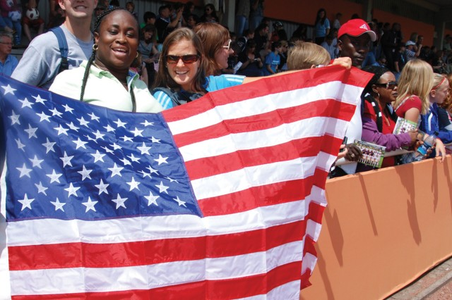 USAG Stuttgart Child, Youth and School Services employees Wesley Drake (front left) and Caitlin Smith, with Clay Elkin (red hat), show their national pride at the U.S. Women's National Team practice June 30, 2011, in Heidelberg, Germany.