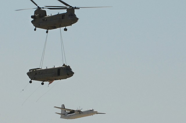 A CH-47F Chinook cargo helicopter from the 1st Air Cavalry Brigade, 1st Cavalry Division, sling loads another Chinook cargo helicopter while another aircraft streams by in the background, July 6, 2011.