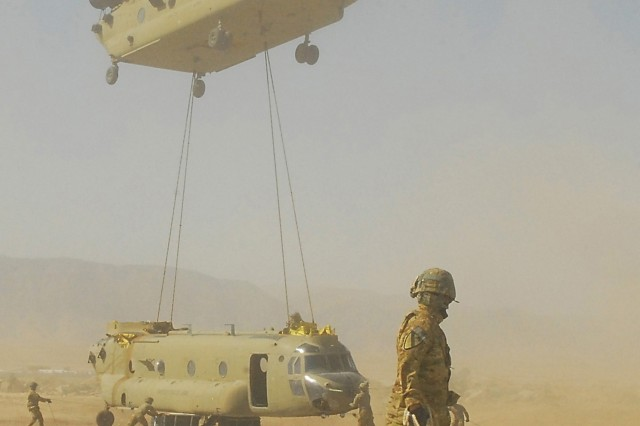 A CH-47F Chinook helicopter from Task Force Lobos, 1st Air Cavalry Brigade, 1st Cavalry Division, lowers a sling-loaded Chinook while crew members from 615th Aviation Support Battalion, 1st ACB, help safely guide the aircraft toward the ground, July 6, 2011