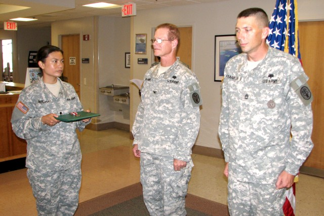 Sgt. 1st Class Gregory Franklin (right), senior dental NCO, prepares to receive a Meritorious Service Medal for assuming additional duties to help prepare the clinic for BRAC closure. McNeme (center), presented the award, held by Spc. Myrna Marcucci, dental assistant.
