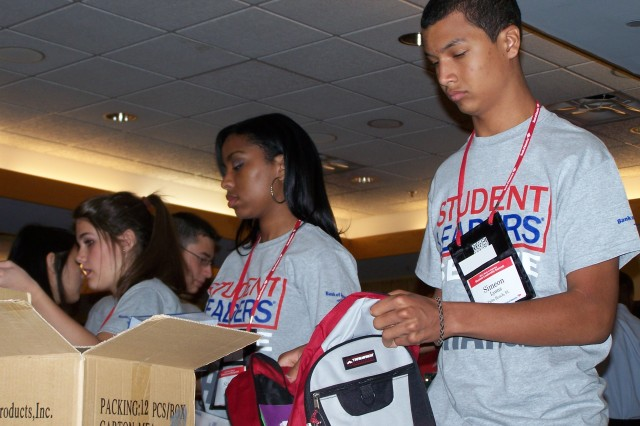 Student leaders help stuff backpacks full of school supplies for military children as part of Operation Homefront at the Washington Navy Yard, July 12, 2011.
