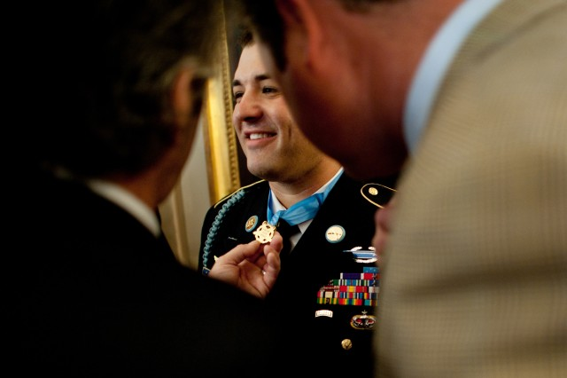 Friends of Army Sgt. 1st Class Leroy Arthur Petry inspect the Medal of Honor he received at the White House in Washington, D.C., July 12, 2011.
