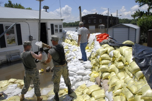 The Active Guard Reserve allows active-duty Soldiers to transfer to locations closer to home, where their skills can be put to good use. Here, Illinois Army National Guard Soldiers reinforce a sandbag wall protecting homes of residents of Hamburg, Ill., during recent flooding along the Mississippi River.