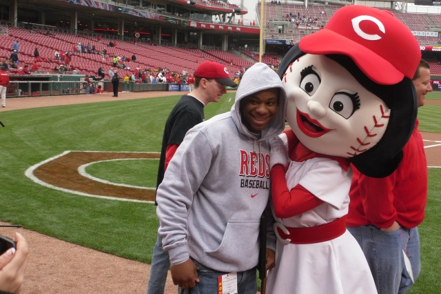 """Spc. Joseph Nelson, 396th Engineer Company, interacts with Rosie Red, the Cincinnati Reds Team mascot, prior to a game against the Houston Astros at Great American Ball Park, May 4, 2011. The Reds made Nelson an honorary captain for the day, and the """"Thank You Foundation,"""" presented him with a Certificate of Appreciation for his service and sacrifice to the country. Nelson suffered a concussion and a knee injury after his Husky route-clearance vehicle hit a roadside bomb during a mission last year in Afghanistan."""