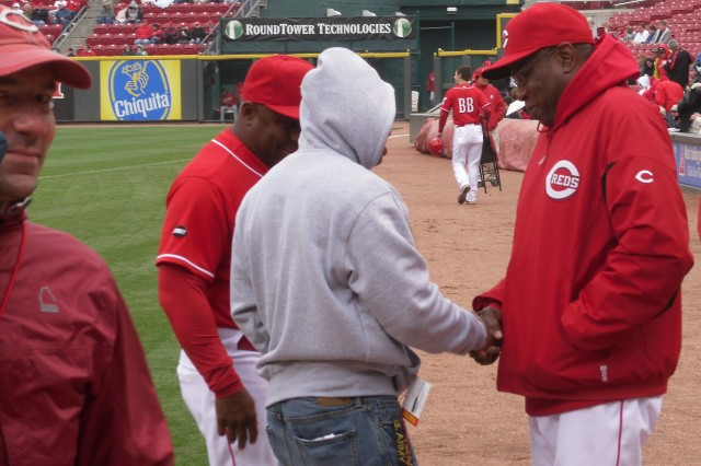 "Spc. Joseph Nelson, 396th Engineer Company, greets Cincinnati Reds Team Manager Dusty Baker at Great American Ball Park prior to a game against the Houston Astros. The Reds made Nelson an honorary captain for the day, and the ""Thank You Foundation,"" presented him with a Certificate of Appreciation for his service and sacrifice to the country. Nelson suffered a concussion and a knee injury after his Husky route-clearance vehicle hit a roadside bomb during a mission last year in Afghanistan."