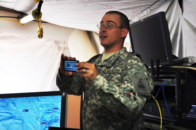 Spc. Nicholas C. Johnson, an Infantryman assigned to Company A, 1st Battalion, 35th Armor Regiment, 2nd Brigade, 1st Armored Division, explains how the smart phone works during the guests visit to Mountain Village at White Sands Missile Range, N.M., June 28, 2011. Military leaders visited the site to see systems under test during the 2/1 AD Network Integration Evaluation.