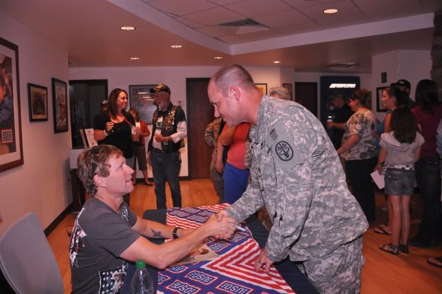 FORT CARSON, Colo. -- Staff Sgt. Rob Abbott, Company A, Warrior Transition Battalion, receives an autograph and a handshake from country music star Craig Morgan at a meet and greet at the USO July 8.