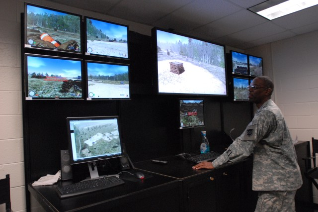 """Sgt. 1st Class Morris Freelon watches multiple TV screens and evaluates how Soldiers are navigating through a scenario in the Virtual Interactive Combat Environmental (V.I.C.E) trainer. Soldiers from the 99th Regional Support Command practiced their Warrior Task skills at the Virtual Interactive Combat Environmental (V.I.C.E) trainer in preparation for the upcoming annual training mission dubbed """"Operation Checkerboard"""". (U.S. Army Photo by Sgt. 1st Class Alyn-Michael Macleod)"""