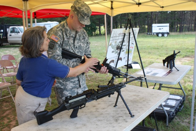 Kori Phillips, an ARDEC systems management engineer, talks to Sgt. Jason Reed about the chamber of the lighter version of the M249 machine gun.
