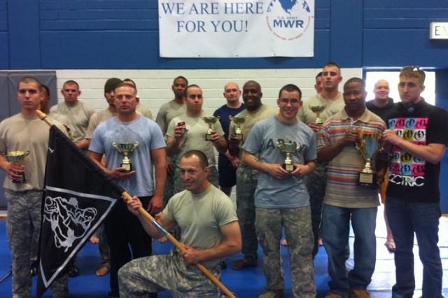 Sgt. Omar Ramirez, a transportation management coordinator with the 16th Special Troops Battalion, 16th Sustainment Brigade, 21st Theater Sustainment Command, holds a Modern Army Combatives Program guidon along with all the Soldiers who placed during the Bavarian Open Combatives Tournament June 25 at Hohenfels, Germany.