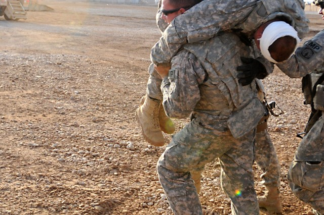 "Soldiers from the 194th Military Police Co., who are supporting 1st Battalion, 325th Airborne Infantry Regiment, carry an ""injured"" battle-buddy to a casualty collection point, following a simulated attack on their convoy, during a training exercise at Camp Ramadi, Iraq, July 15. (U.S. Army photo by Sgt. 1st Class Seth Laughter, 2/82 PAO NCOIC)"