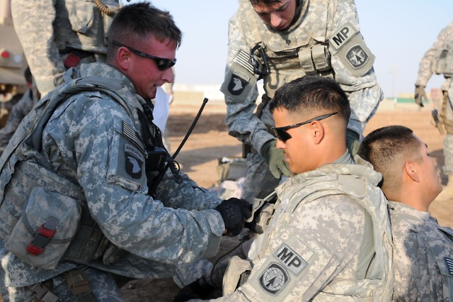 "A Soldier from the 194th Military Police Co., who are supporting 1st Battalion, 325th Airborne Infantry Regiment, pulls a release cable to remove the body armor of a fellow Soldier so he can treat his ""injuries,"" during a training exercise at Camp Ramadi, Iraq, July 15. (U.S. Army photo by Sgt. 1st Class Seth Laughter, 2/82 PAO NCOIC)"