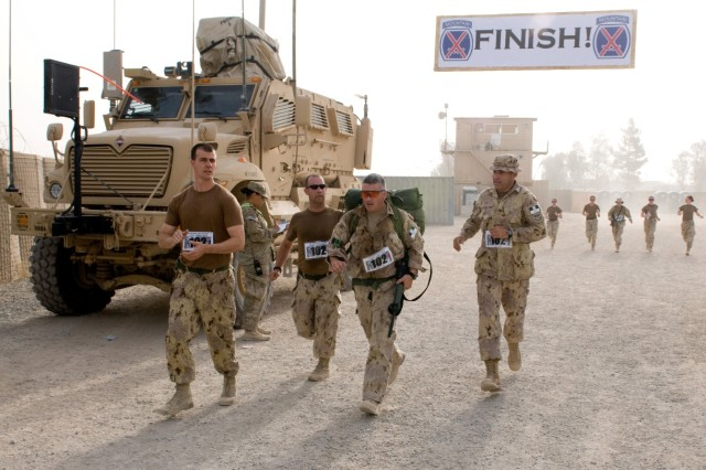 KANDAHAR AIRFIELD, Afghanistan – Canadian servicemembers cheer as a competitor crosses the finish line during the 10th Mountain Combat Relay Run held on Kandahar Airfield, Afghanistan, July 17, 2011. More than 110 teams competed in the relay representing nine different countries, including three teams from the Afghan National Security Force. (U.S. Army Photo by Staff Sgt. Jes L. Smith, 16th Mobile Public Affairs Detachment)