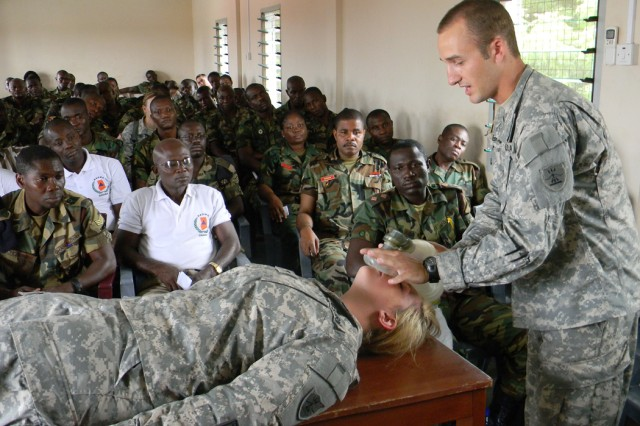 National Guard medics from the 814th Medical Company, Sgt. Zach Brainert from Fargo, N.D., and Spc. Amanda Schumacher from Hope, N.D., demonstrate rescue breathing with a bag-valve-mask July 14, 2011, at Burma Camp, Accra, Ghana during MEDFLAG 11.