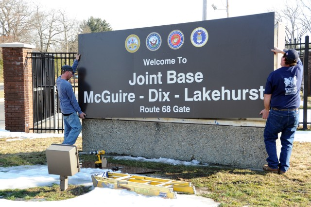 Workers post the sign for Joint Base McGuire-Dix-Lakehurst after McGuire Air Force Base, Fort Dix and Lakehurst Naval Air Engineering Station in New Jersey merged on Oct. 1, 2009, to become the Defense Department's only tri-service base.