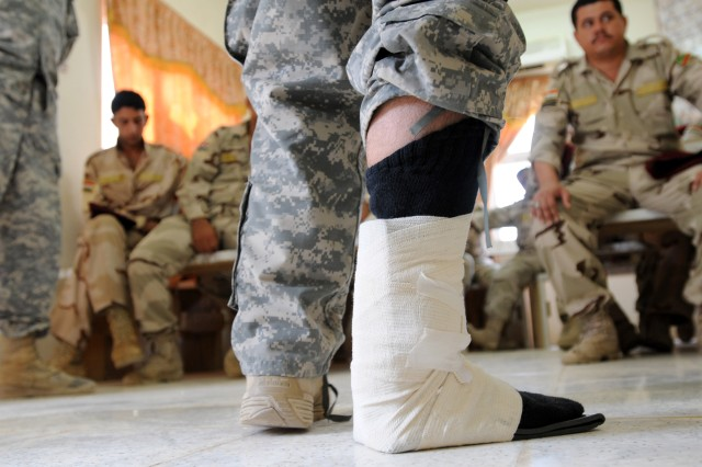 "With a ""sprained ankle"" properly treated, Private 1st Class James Ladina, a medic with C Co., 407th Brigade Support Battalion, 2nd Advise and Assist Brigade, teaches a class of 7th Iraqi Army Division medics about clinical orthopedics at the IA compound on Al Asad Air Base, July 11. Ladina, a native of Belleville, MI, simulates this injury for each group of medics he trains to test their reaction time and their knowledge of the treatment of orthopedic injuries. As one of the few units to have taken part in every major campaign of the U.S. military's operations in Iraq, the 2/82 has been tasked with strengthening the Iraqi Security Forces as they work to maintain a safe and secure environment for the Iraqi people as the 2/82 leads the transition of U.S. Forces out of Iraq.  (U.S. Army photo by Sgt. Kissta M. Feldner, 2/82 PAO)"