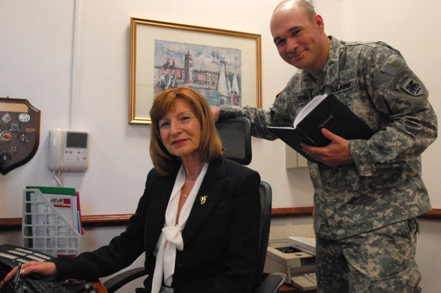 Commander's secretary, Vera Frater (left), and Sgt. Ken Turman pose for a photo in the U.S. Army Africa command section.  Frater has worked for eight commanding generals over the past 13 years.  She will soon retire with more than 17 years as a Department of the Army civilian. Frater and her husband Adeal will make a new home in Florida where they will be close to grandchildren and other family members.