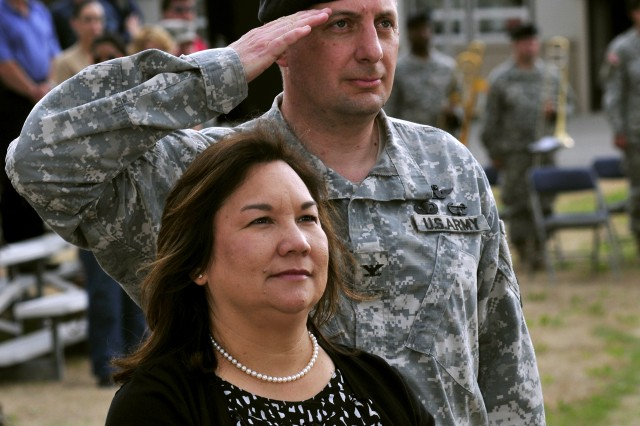 Col. Timothy Jones salutes standing with wife Theresa Jones as the flag lowers during retreat on Fort Wainwright July 8. Jones was presented the flag which had flown over Fort Wainwright in his honor as he retires after 27 years of Army service. (Photo by Brian Schlumbohm/Fort Wainwright PAO)