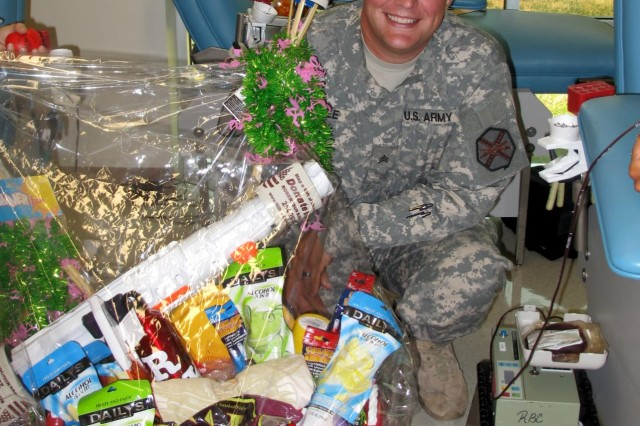 Sgt. Justin Caple poses with the gift basket he won for supporting the Texas Shootout at the Robertson Blood Center at Fort Hood, Texas, on June 29, 2011.