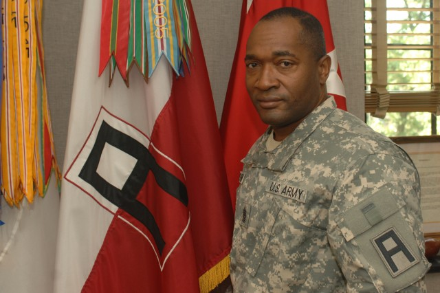 U.S. Army Command Sgt. Maj. Jesse L. Andrews Jr. stands next to the First Army Colors.
