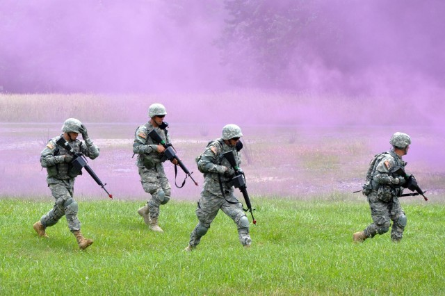 Army privates, shielded by a purple smoke screen, attempt to ambush insurgents during a training exercise at Edgewood's EST 2000.