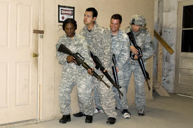 HRED's Samantha Wallace, left, leads an all-civilian combat team on a room clearing mission as part of Greening Course training.